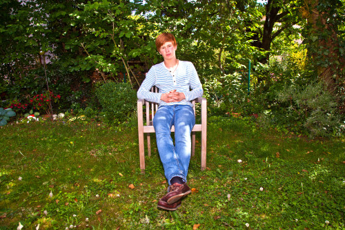 boy sitting on an armchair in his garden
